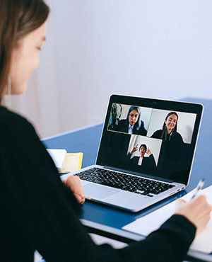 woman looking at laptop during a virtual meeting with a screen that shows video of meeting participants