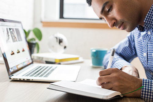 Man writing in a notebook while working at his desk