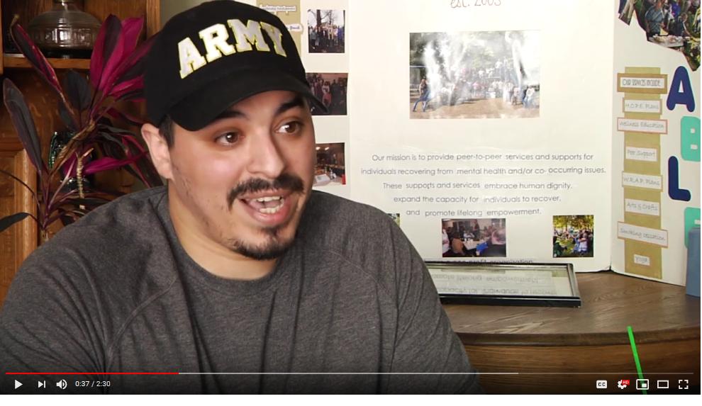 man wearing Army cap speaking
