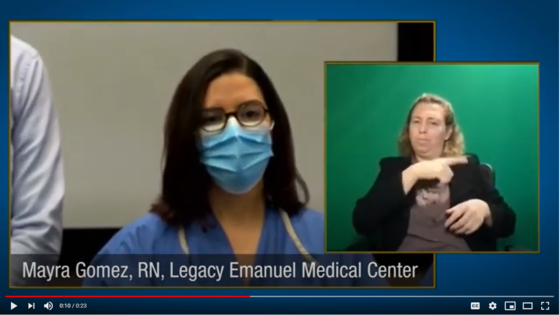 woman in mask and scrubs speaking and sign language interpreter