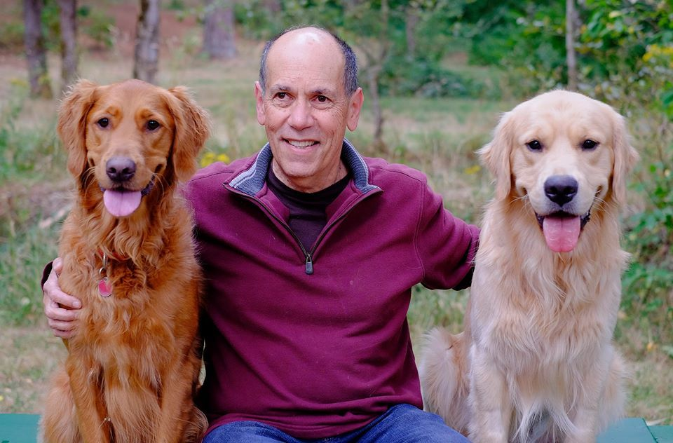 Man smiling and kneeling between two Golden Retriever dogs in the grass with his arms around each dog on either side.