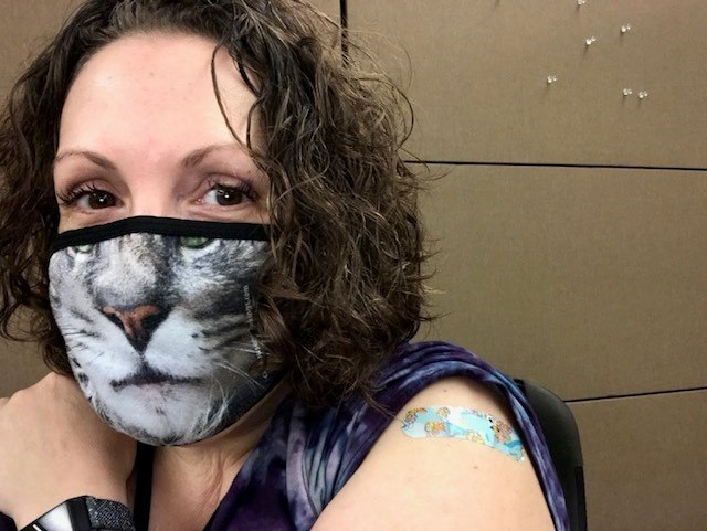 Person wearing facemask that has the face of a tiger on it. Sleeve is rolled up showing a bandage on her shoulder.