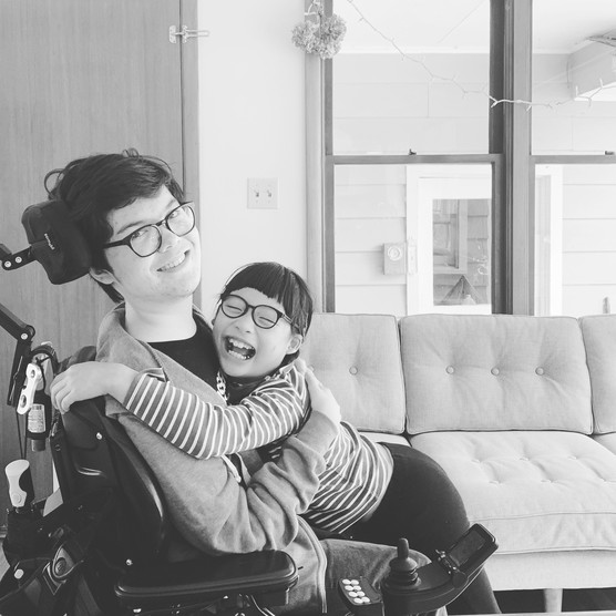 Liam seated in wheelchair smiles at the camera. Sister, Ada, hugs Liam and laughs with eyes closed.
