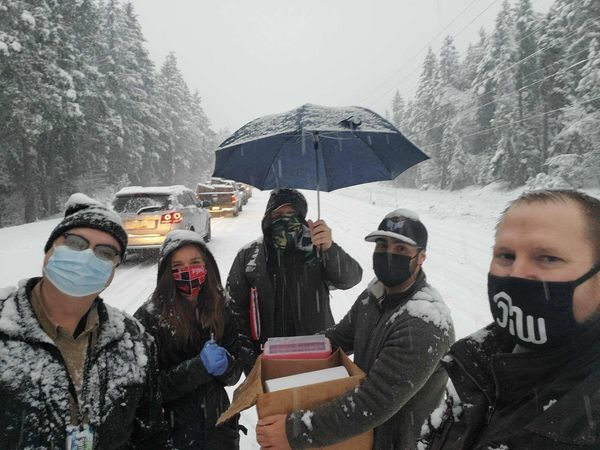 Five people wearing masks, holding a box with one holding an umbrella standing on a snow-coverd street. Cars lined up behind them. Snow is falling.
