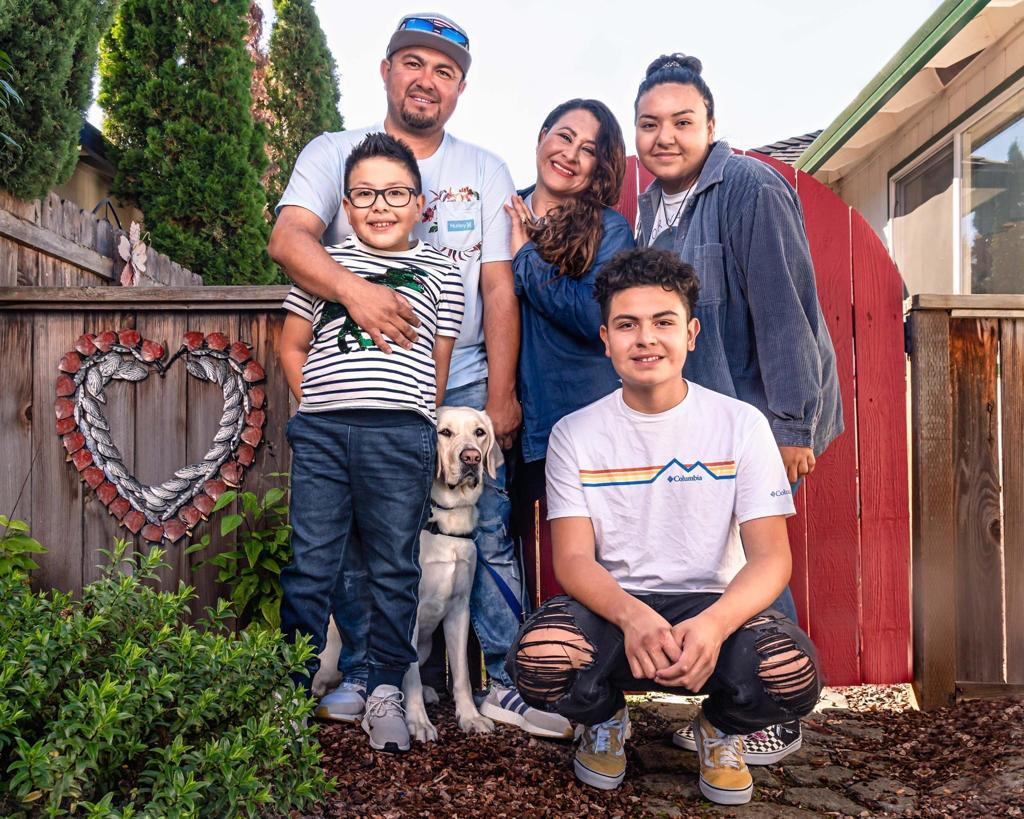 Family of five and a dog posed in front of fence next to a heart art piece.