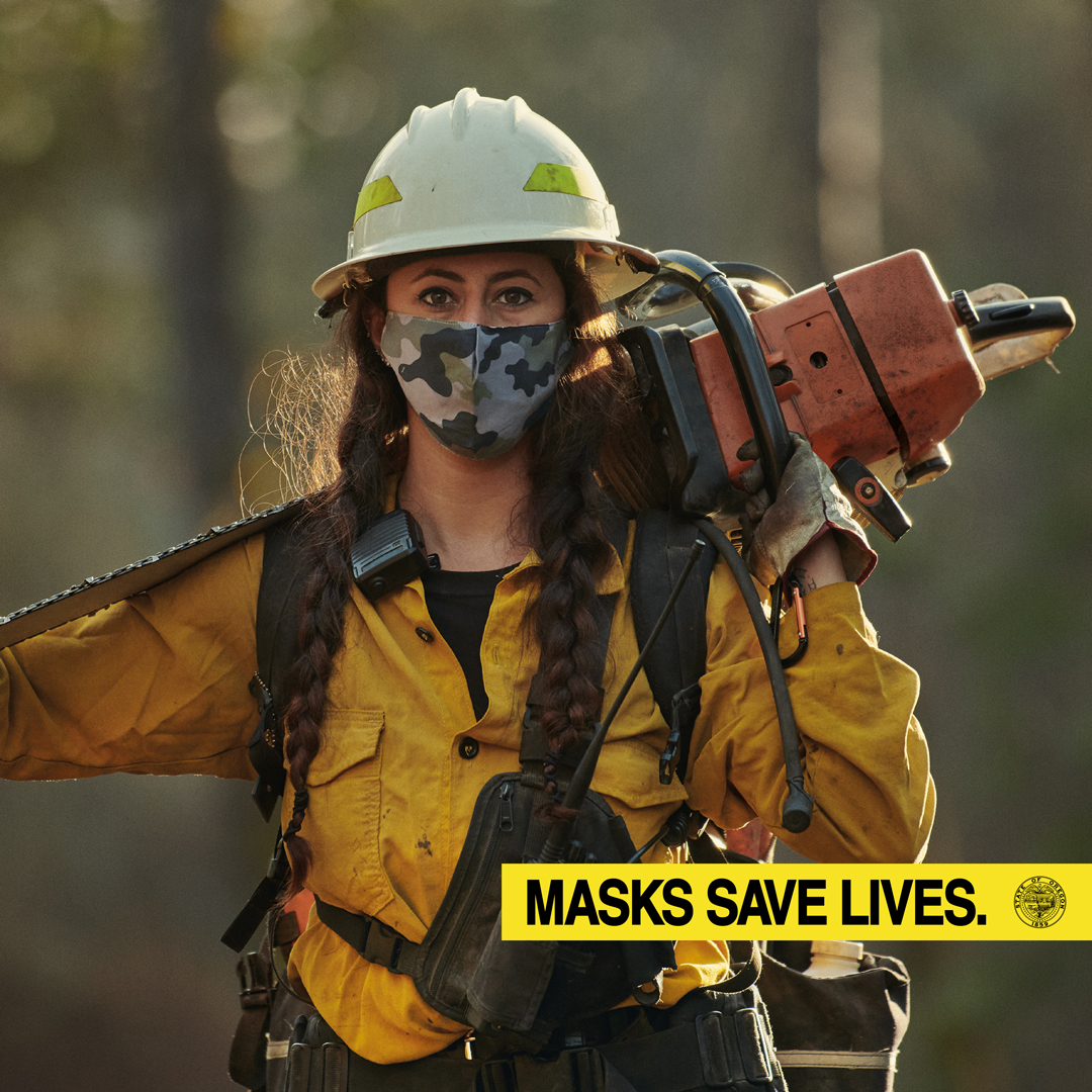 Woman in yellow jacket with long hair, camo mask, hardhat and large chainsaw over shoulder. Yellow banner on photo saying Masks Save Lives.