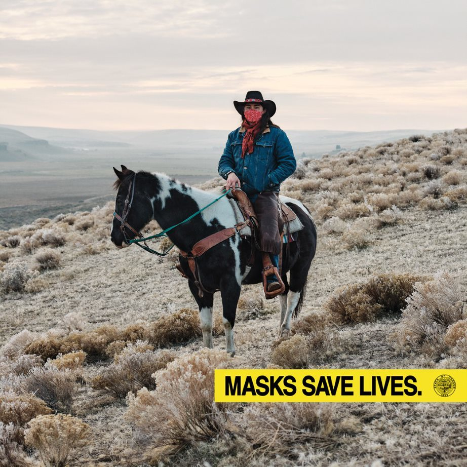 Man with long, black hair, mask, cowboy hat, denim jacket on black and white horse holding reins on a desert mountain. Masks save lives.