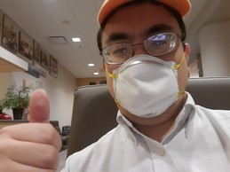 Youngman with glasses, yellow baseball cap and mask on holding his thumb up.