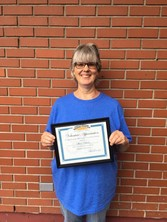 """Woman wearing glasses and smiling as she stands in front of brick wall holding certificate that says """"Volunteer Appreciation""""."""