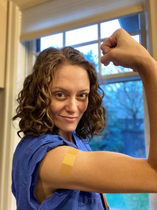 Dr. Lincoln wearing scrubs and showing off her bandaid by flexing her bicep.