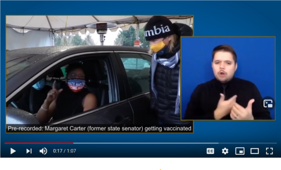 """Women in car with red, white and blue face mask that reads """"Hate has no home here"""" gestures with finger raised."""