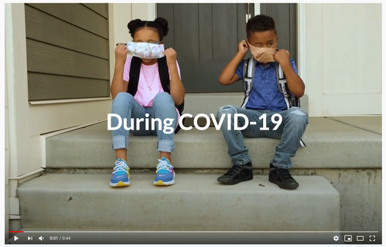 Two children wearing masks and sitting on front steps. Click for video.