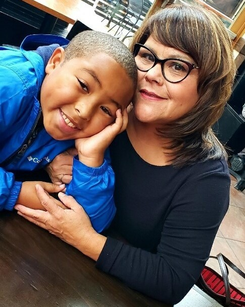 Woman and boy close together smiling at the camera in cafe.