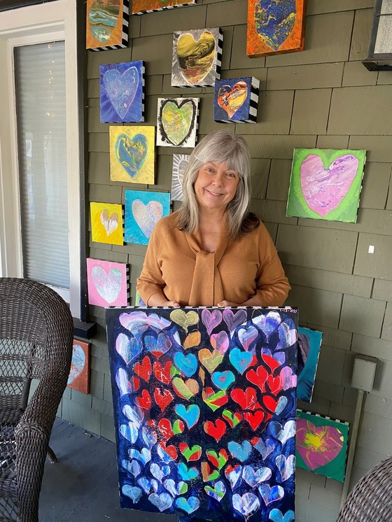 Women standing in front of house with canvas fullof painted hearts and many painted hearts hanging on the wall of her porch.