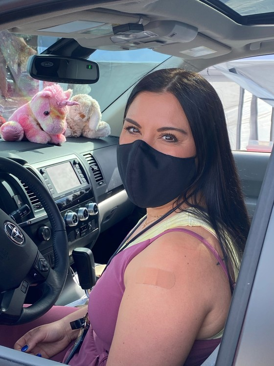 Woman sits in car with bandage on shoulder wearing a black face mask. The dashboard has a stuffed rainbow unicorn and a stuffed bunny toy.