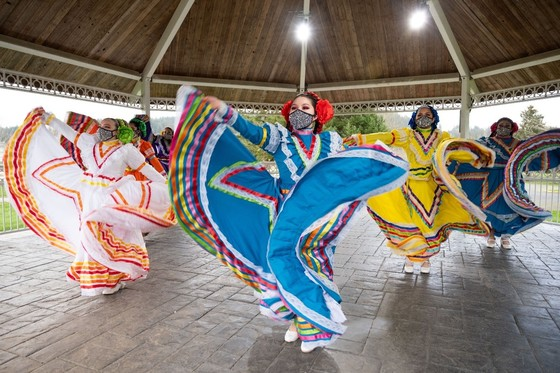 Several dancers wearing colorful dresses, masks and flowered headbands swirl and lift their skirts as they dance in an outdoor gazebo