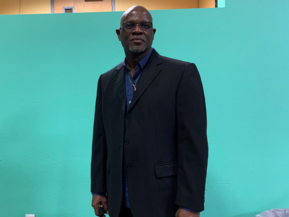 Executive pastor edward williams standing in front of a wall