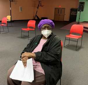 Woman wearing purple beret, white mask and glasses sits in a room  with empty chairs spaced far apart holding some papers.