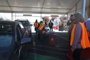 Governor Kate Brown wearing safety vest along with other volunteers at drive through clinic.
