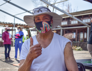 Farmworker wearing a white t-shirt, sunhat with goggles on it, and a facemask with a colorful religious figure of a madonna on it holds his thumb up.