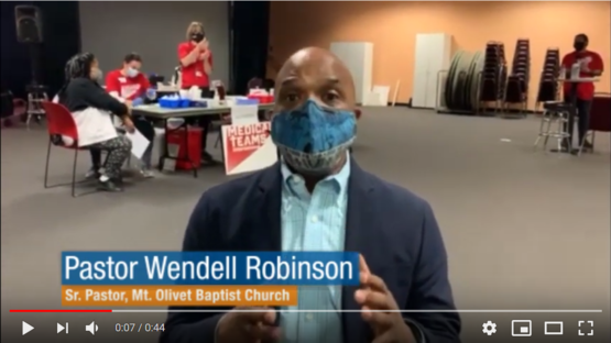 Man wearing face mask at vaccine clinic.