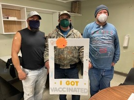 """Three people wearing masks, work clothes and baseball caps holding a sign that says """"I got vaccinated""""."""