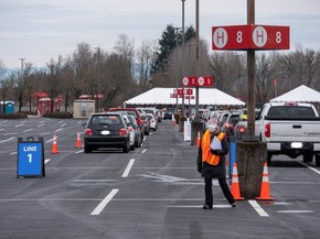 Parking lot with red signs, two lines of cars and a worker wearing a safety vest.