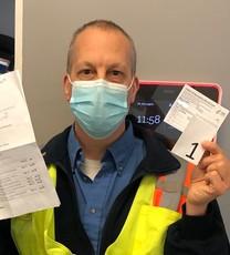 Person wearing mask in TriMet uniform holding immunization card.