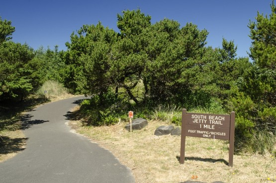 """Paved curving path surrounded by gree trees and wooden sign that says """"South Beach Jetty Trail 1 mile""""."""