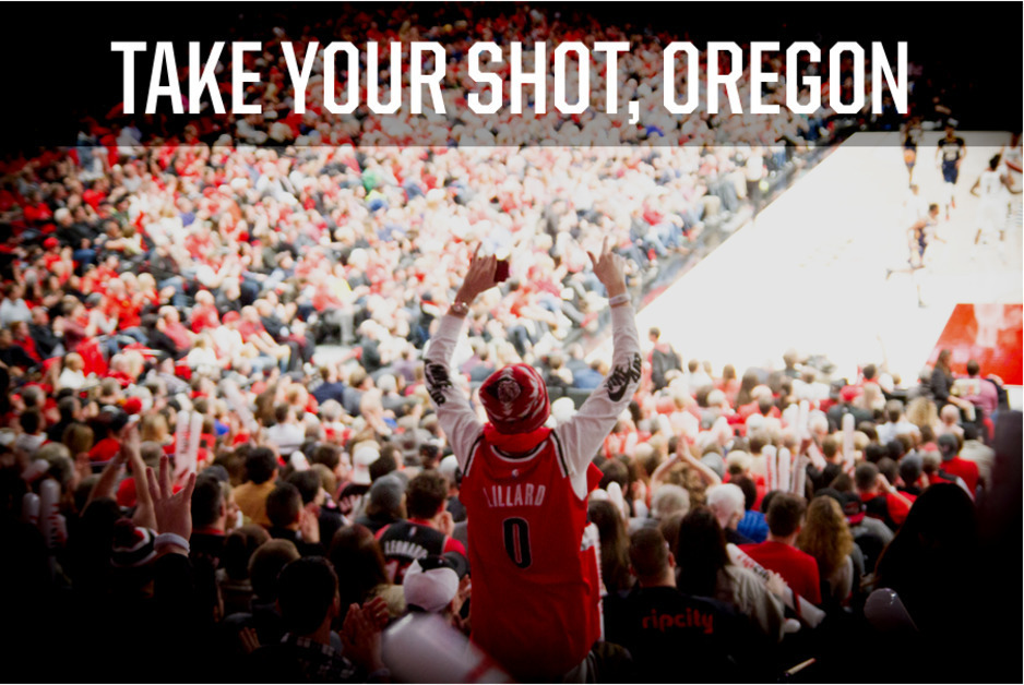 """FAn in the stands at Blazer game wearing Lillard shirt, hands raised with text saying """"Take your shot, Oregon""""."""