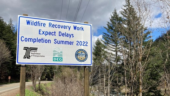 """Roadside sign says """"Wildfire Recovery Work Expect Delays Completion Summer 2022"""""""
