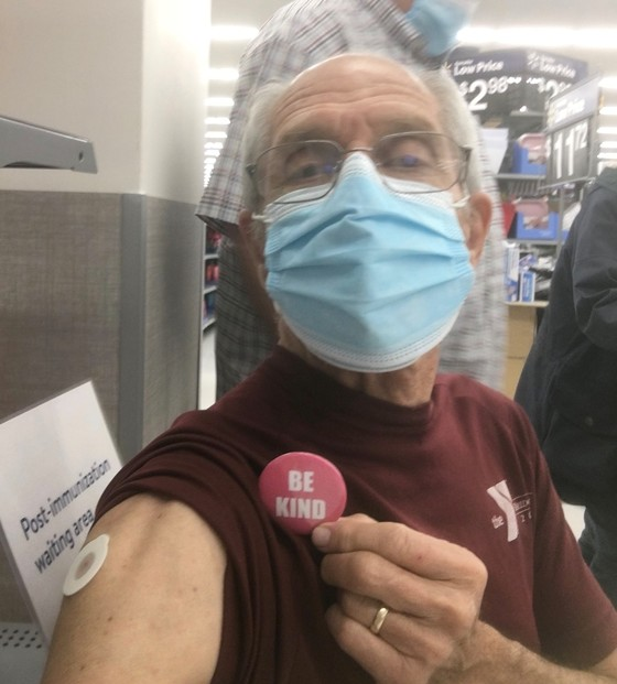 Man in mask wearing a Be KInd pin