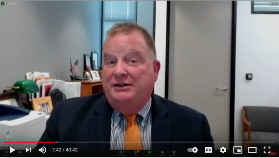 Video screenshot of OHA Director Patrick Allen wearing suit and tie and talking with an office showing in the background.