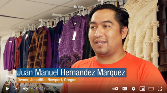 Video screenshot of a man wearing an orange t-shirt standing in front of a rack of sweaters in a variety of colors.