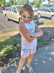 Girl wearing sunglasses, tank top, striped shorts and sandals poses with arms crossed and smiles.