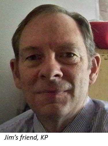 Man with gentle smile and short brown hair wearing a striped oxford shirt.