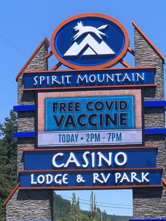 Sign with graphic of animal leaping over a mountain that says Spirit Mountain Casino FREE COVID VACCINE with blue sky and trees in background.
