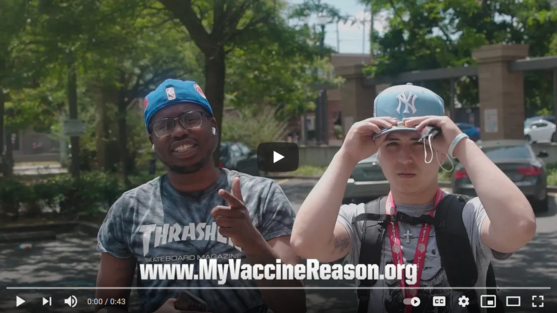 Two young people in baseball caps and grey t-shirts. One pointing and smiling at camera and the other has hands on brim of cap. Trees in background.