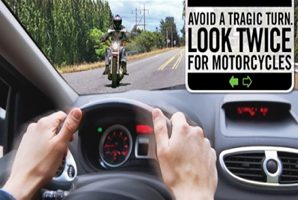 Text: Avoid a tragic turn. Look twice for motorcycles. Image: Car driver with left signal on and motorcycle approaching.