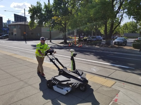 Man uses survey equipment on a street