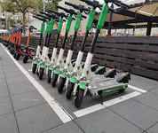 E-scooters in a row on a sidewalk for rental