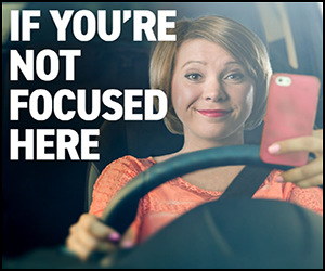 """Text: """"If you're not focused here."""" Woman driving with cell phone in hand."""