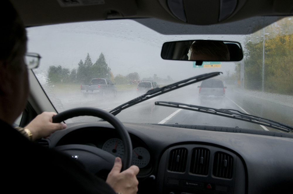 Driver behind the wheel with windshield wipers on during the rain