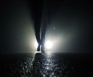 Vehicle with headlights on in fog with pedestrian in the roadway