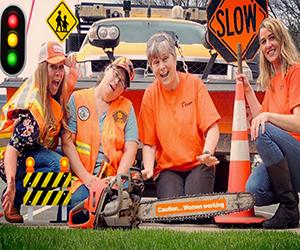 "Staff wearing orange with traffic sign ""slow"""