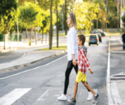 Woman and child walking across the street in a crosswalk.