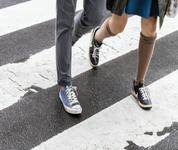 Two people crossing the street in a marked crosswalk.
