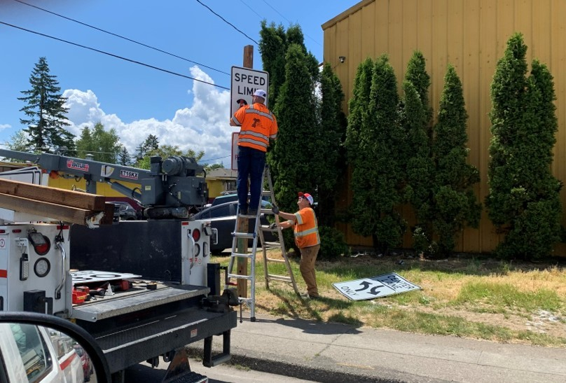 Workers install new speed limit signs on 82nd Avenue