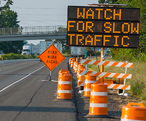 """Construction zone on highway with VMS sign """"WATCH FOR SLOW TRAFFIC"""""""