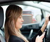 Woman driving while looking at her phone